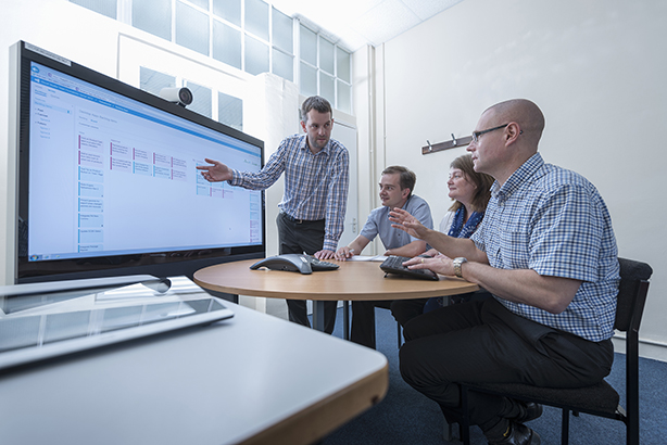 Software engineers holding a meeting around an interactives surface