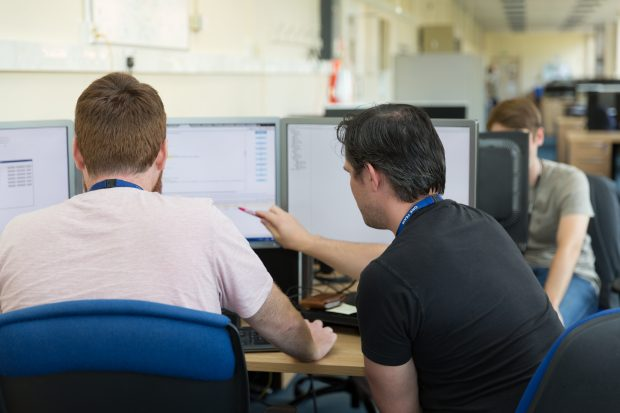 Two software developers working together at a computer
