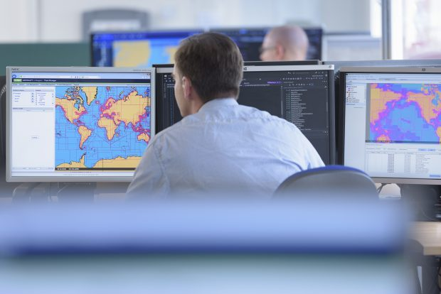 UKHO worker looking at code and geospatial data on a screen