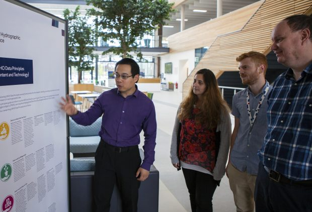 A UKHO staff member presenting the data principles to three other staff members in the UKHO building