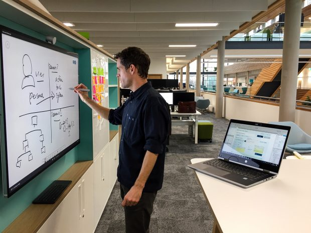 User experience lead reviewing user design system on whiteboard at the UK Hydrographic Office